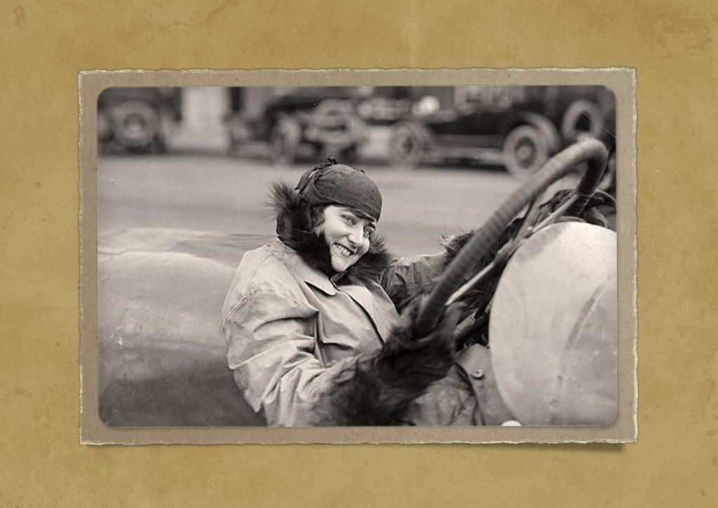 Auf einem antiken Foto wird eine Dame hinter dem Steuer eines Autos gezeigt. Feedbackfahrt